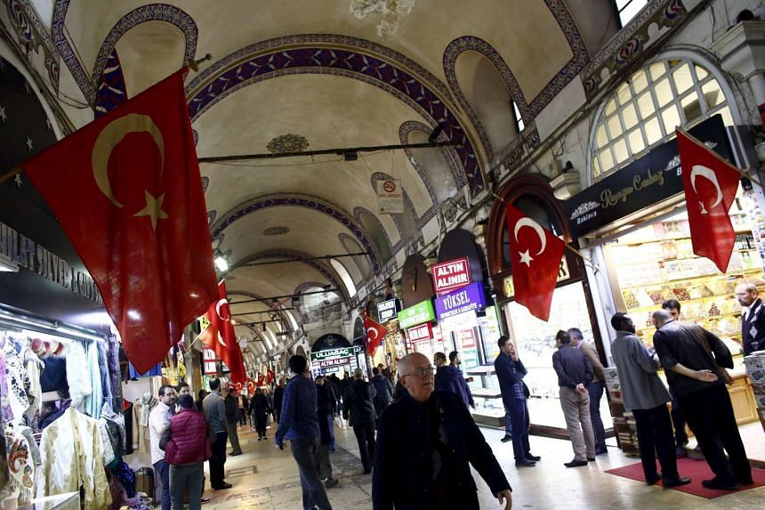 People visit the shops of gold dealers as local and foreign tourists stroll through the Grand Bazaar in Istanbul, Turkey, on March 22, 2016.