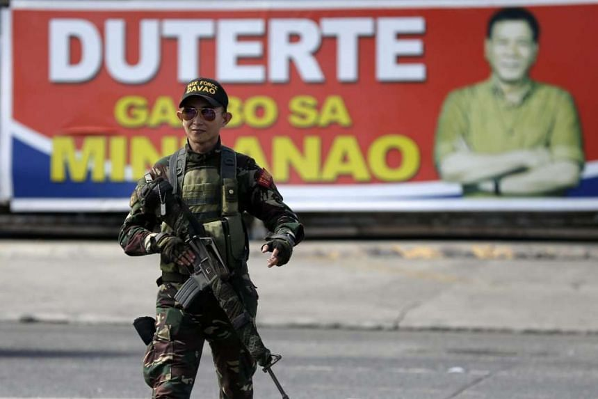 A Filipino soldier patrols a street next to the banner of presumptive President-elect Rodrigo Duterte in Davao City, on May 16, 2016.