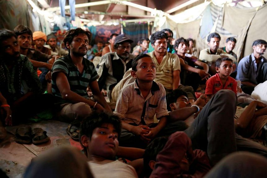 People watch a movie in a makeshift cinema located under a bridge in the old quarters of Delhi, India, on May 25, 2016.
