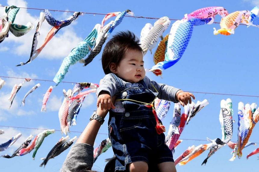 A father holds up his baby under carp streamers fluttering in a riverside park in Sagamihara, Tokyo, on April 29, 2016.