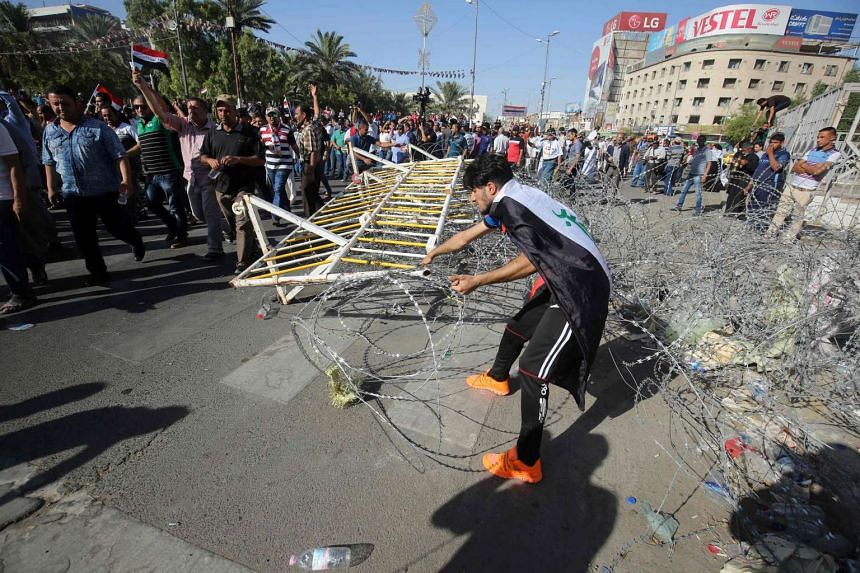 A supporter of Iraqi cleric Moqtada al-Sadr removes barbed wire as demonstrators make their way towards Baghdad's fortified Green Zone, on May 20, 2016.