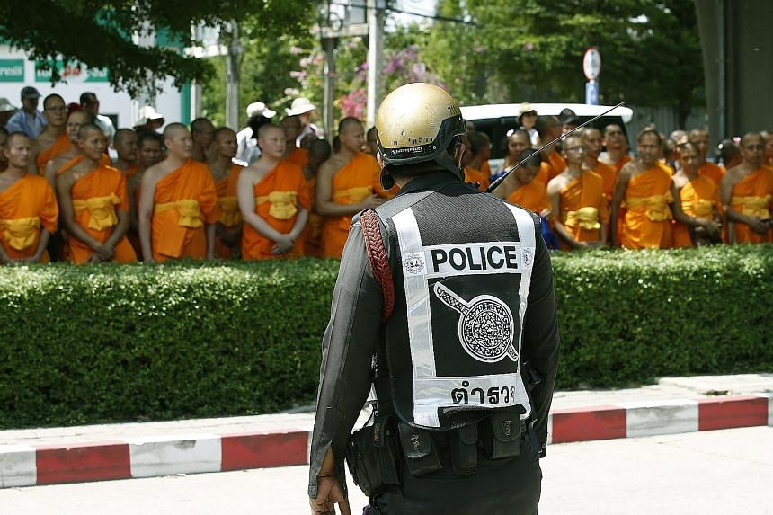 A Thai policeman standing guard yesterday at the Khlongluang provincial police station in Pathum Thani province as Buddhist monks waited for Phra Dhammachayo, the abbot of the controversial Dhammakaya temple, to turn up to face charges of money-laund