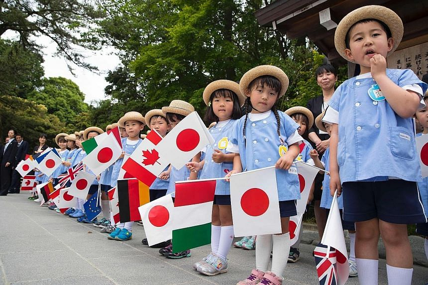 Schoolchildren and officials waiting to welcome G-7 leaders in the city of Ise yesterday for their tour of Ise Grand Shrine, which is considered one of the holiest sites in Japan's native Shinto religion. Mr Obama and Mr Abe being received by Shinto