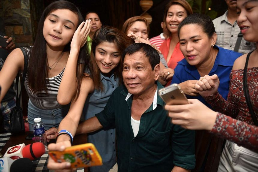 Philippines' President-elect Rodrigo Duterte poses for selfie pictures with supporters at a restaurant in Davao City, on the southern island of Mindanao on May 15, 2016.