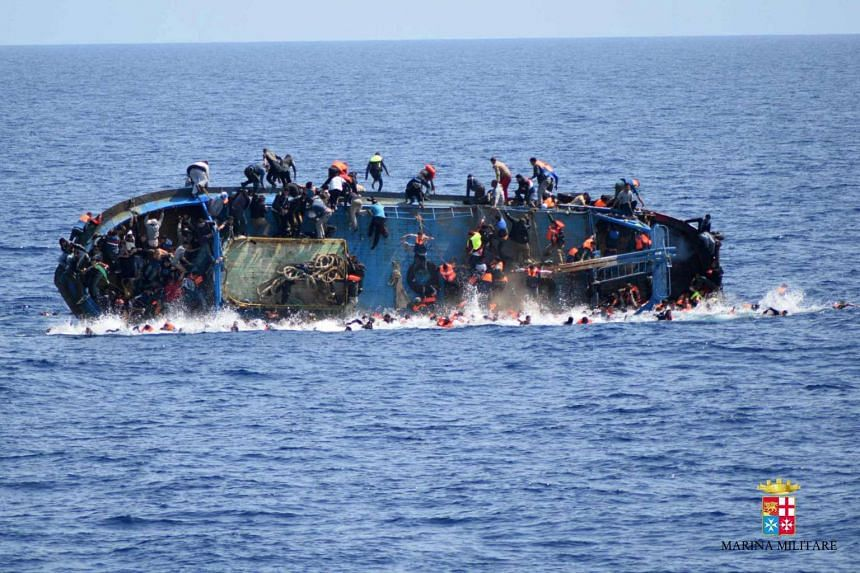 The boat overturning in photos released by the Italian authorities.