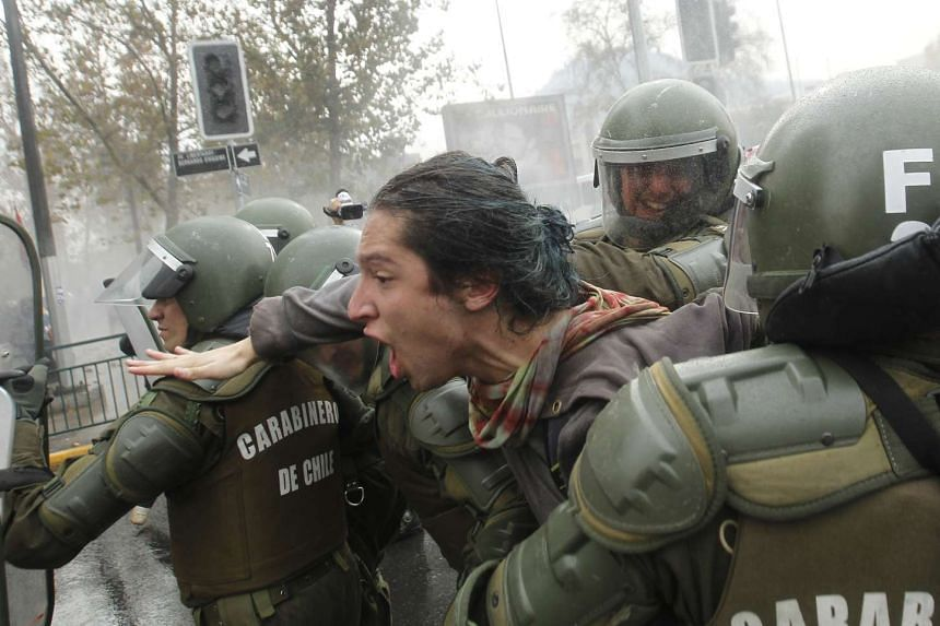 Riot police arrest a student during a march against the slow pace of educational reform, in Santiago, on May 26, 2016.