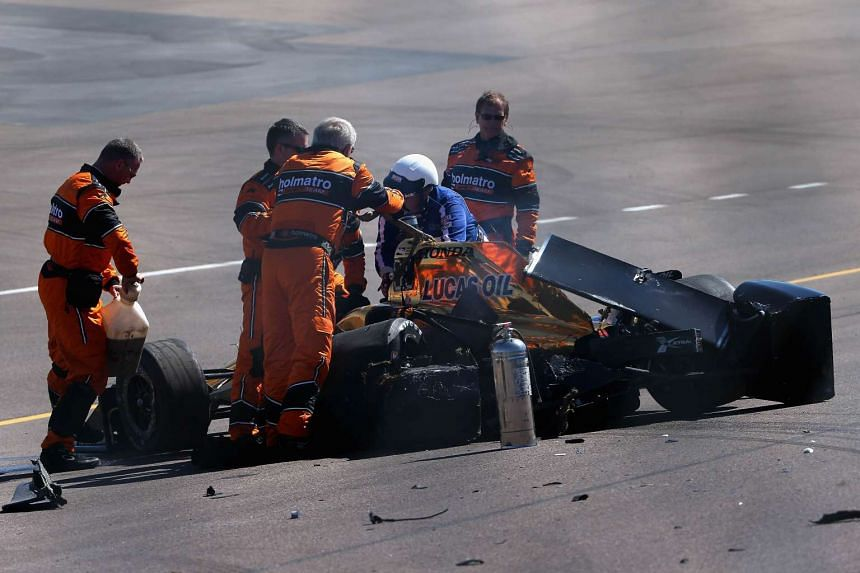 Canadian driver James Hinchcliffe is helped by safety crew after a wreck during practice for the Phoenix Grand Prix on April 1.