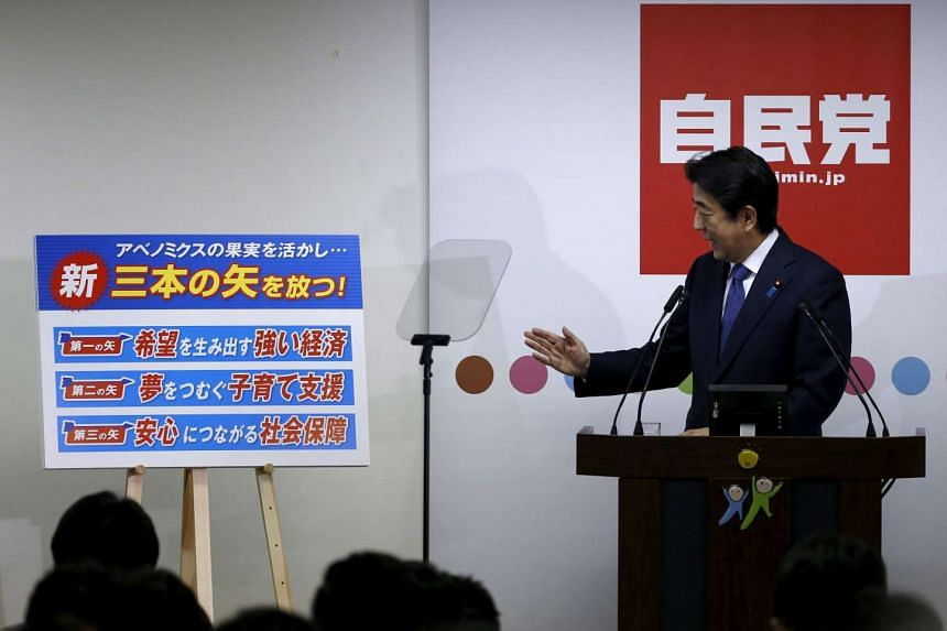 """Japan's Prime Minister Shinzo Abe explains his three new arrows of """"Abenomics"""" policy, during a news conference at the party headquarters in Tokyo Sept 24, 2015."""