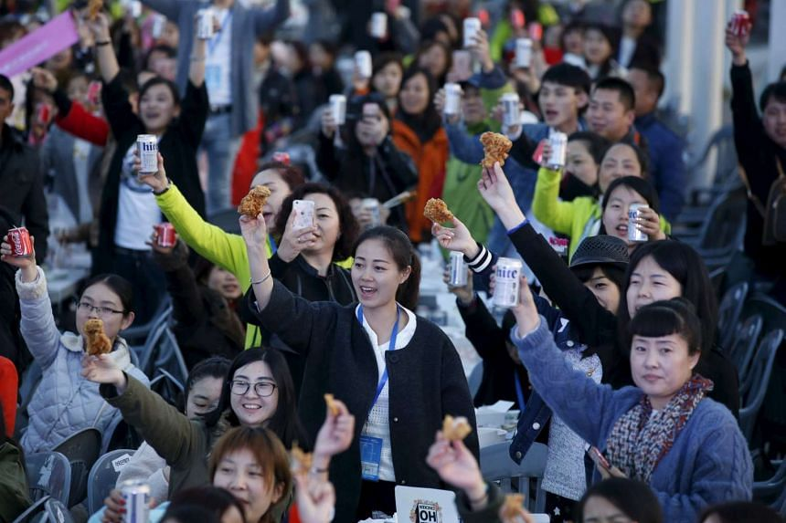 Chinese tourists make a toast with canned drinks and fried chicken at an event at a park in Incheon, South Korea, on March 28, 2016.