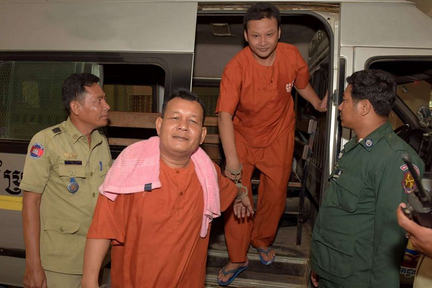 Sot Vanny (left) and Mao Hoeun (right) are escorted by police officials at Phnom Penh's municipal court on April 28, 2016.
