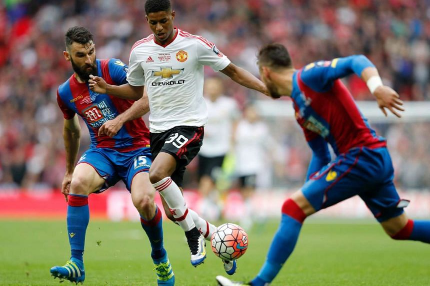 Manchester United's striker Marcus Rashford (centre) vies with Crystal Palace's midfielder Mile Jedinak (left) during the English FA Cup, on May 21, 2016.