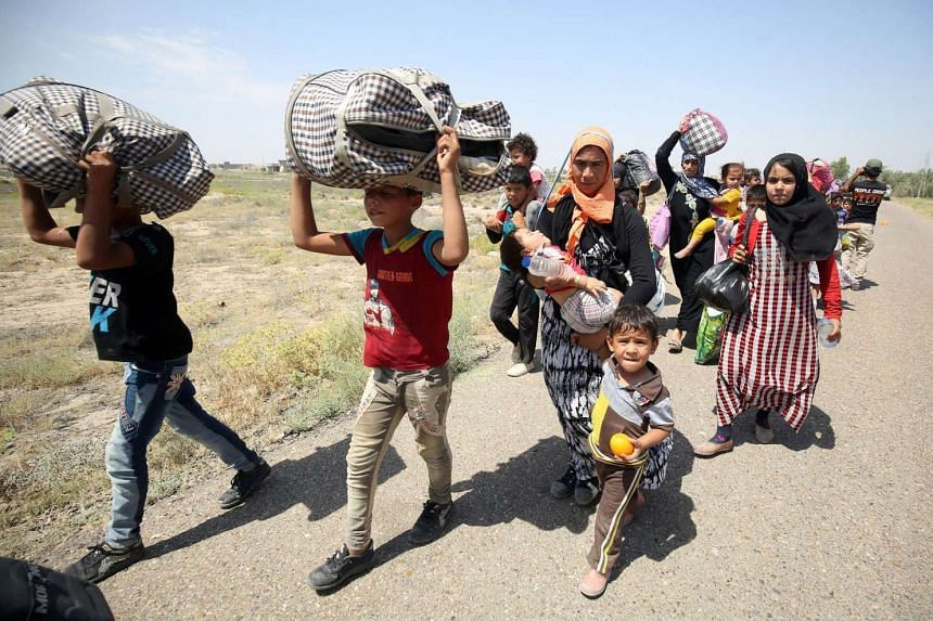 Iraqi families are pictured near al-Sejar village, in Iraq's Anbar province, after fleeing the city of Fallujah, on May 27, 2016, during a major operation by Pro-government forces to retake the city of Fallujah, from the Islamic State of Iraq and Syr