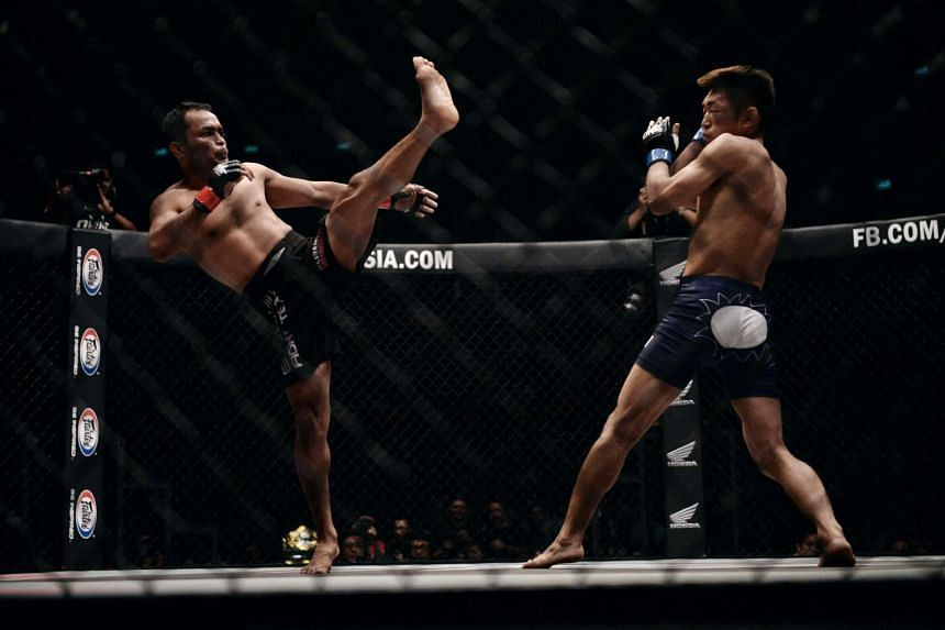 Japanese MMA fighter Yoshitaka Naito (right) avoids a kick from Thai fighter Dejdamrong Sor Amnuaysirichoke (left) during their title bout at the first ever One FC event in Bangkok on May 27, 2016.