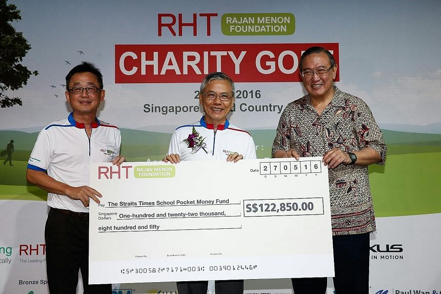 The Straits Times School Pocket Money Fund (SPMF) board trustee, Mr Gerard Ee (right), received a cheque for $122,850 on behalf of the fund from RHT Rajan Menon Foundation chairman Tan Chong Huat (at left) and the foundation's patron, Associate Profe