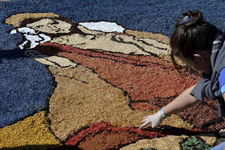 A woman from the Archdiocese of Brasilia creating a religious artwork using sawdust, sand and salt on Thursday to celebrate Corpus Christi, a major Catholic festival and a public holiday in Brazil.