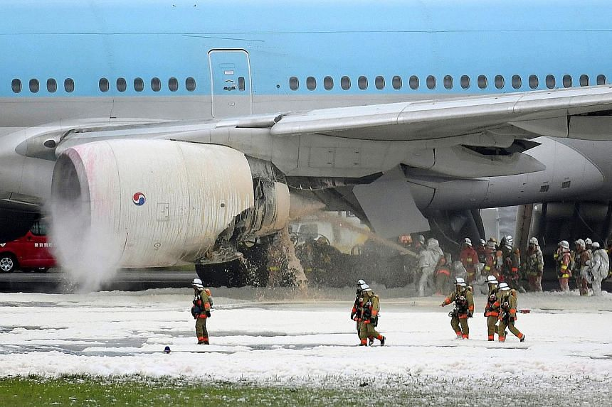 Japanese firefighters spraying foam into the engine of a Korean Air jet that caught fire as the aircraft was preparing to take off from Haneda Airport in Tokyo yesterday. All 319 passengers and crew were evacuated safely. The fire in the left engine