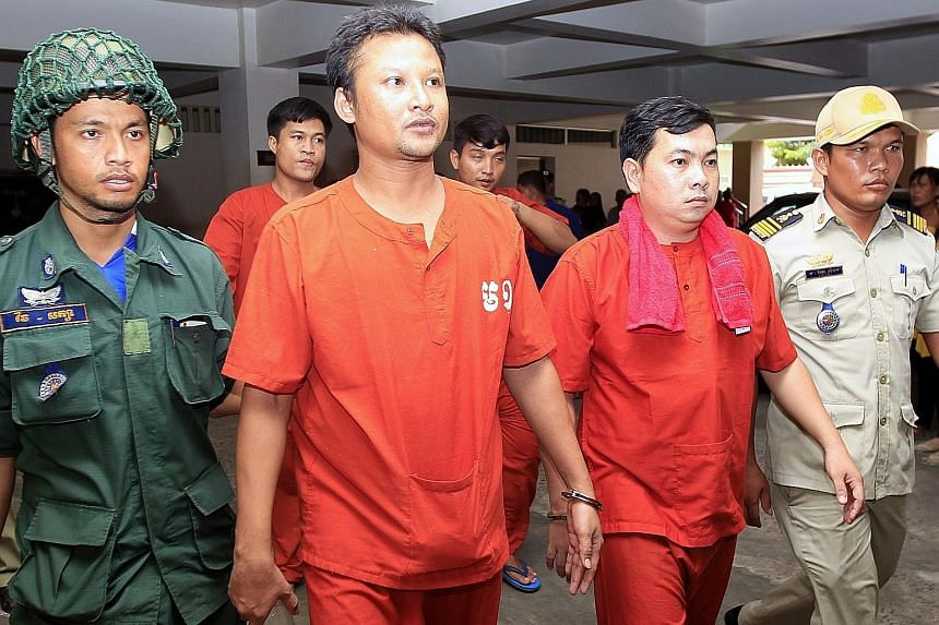 Mao Hoeun (left) and Chay Sarit (right) under police escort at the municipal court in Phnom Penh yesterday. The court has jailed the two men, as well as Sot Vanny, for a year over their attack on two opposition politicians, but the opposition says th