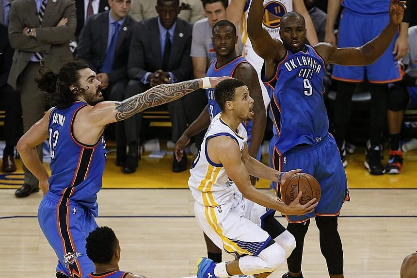 Warriors guard Stephen Curry going to the basket, as Thunder's Kiwi centre Steven Adams (left) and Congolese forward Serge Ibaka defend during Game 5 of the NBA Western Conference finals. Golden State won 120-111 but still trail 2-3 in the best-of-se