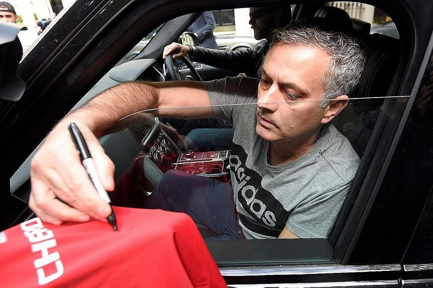 """Jose Mourinho signs a Manchester United football shirt held out by a fan, while being driven from his home in London yesterday. """"To become Manchester United manager is a special honour in the game,"""" he said."""