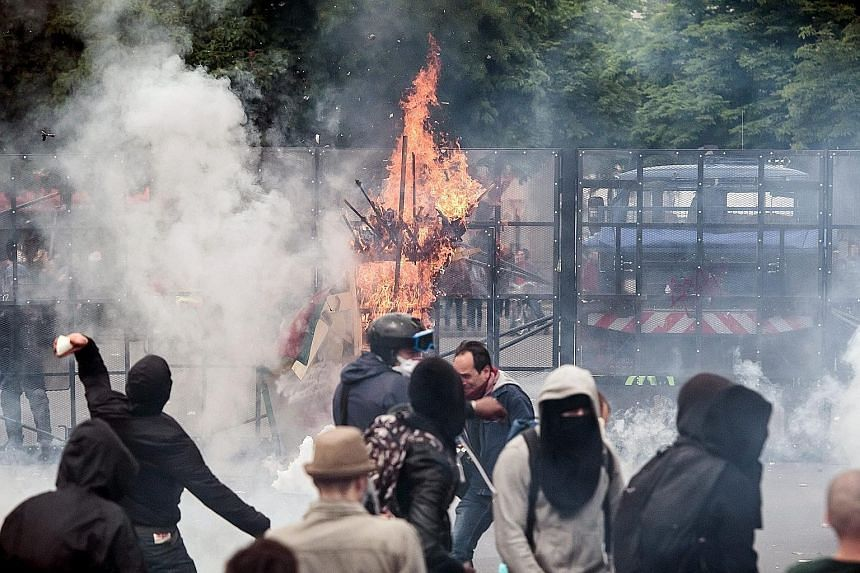 Demonstrators (above) clashing with French riot police in Paris during a protest against the government's labour market reformson Thursday. The unrest also resulted in smashed shop windows (above right) as well as damage to parked cars.
