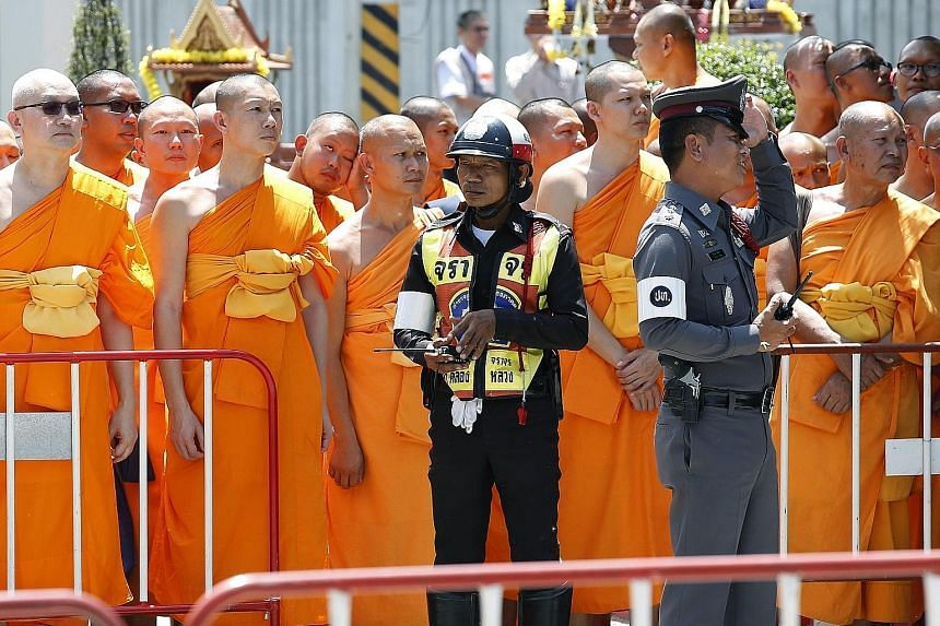 Buddhist monks waiting for Phra Dhammachayo (above) to arrive at the Khlongluang provincial police station in Pathum Thani province on Thursday. The abbot had agreed to hear charges at the police station but did not show up, reportedly having fainted