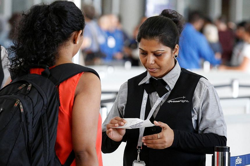 A private contractor preparing a passenger at a security checkpoint at JFK airport in New York on May 27.