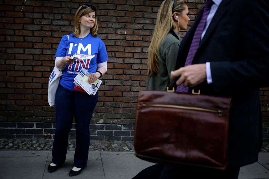 """A woman hands out leaflets campaigning to stay in Europe for the """"Brexit"""" vote in London, Britain, May 20, 2016."""