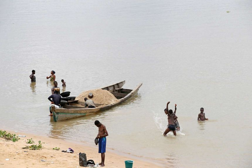 A canoe loaded with sand is anchored on the creek of river Nun as people bathe near a jetty in Yenagoa, in Nigeria's Delta region, on May 19, 2016.