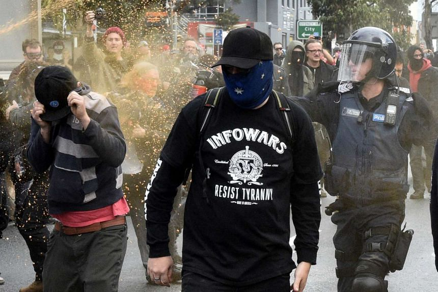 A policeman deploys capsicum spray towards a protester during clashes in the Melbourne suburb of Coburg, Australia, on May 28, 2016.