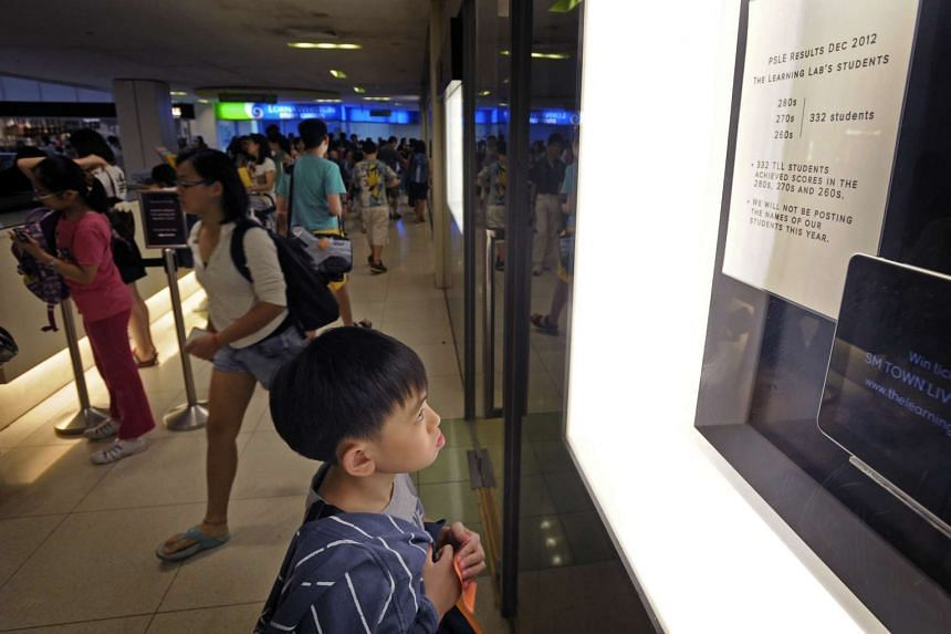 A boy looking at a notice outside a tuition centre in United Square.