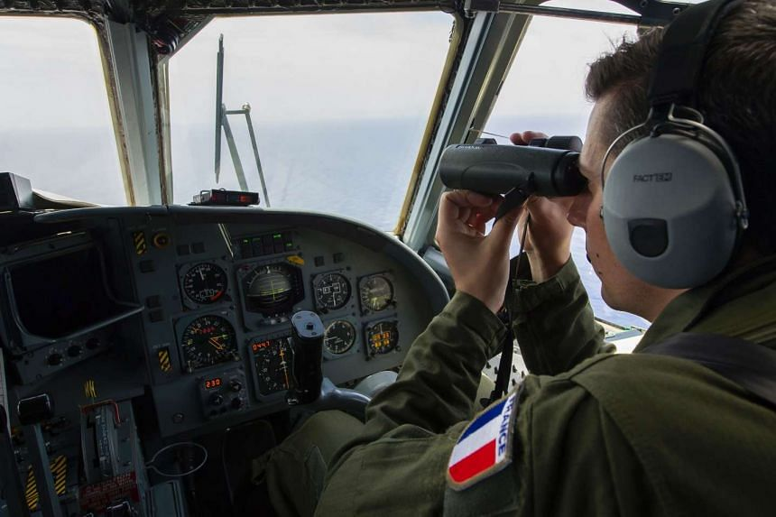 A French soldier aboard an aircraft looking through binoculars to search for debris from the crashed EgyptAir flight MS804 over the Mediterranean Sea, on May 22, 2016.