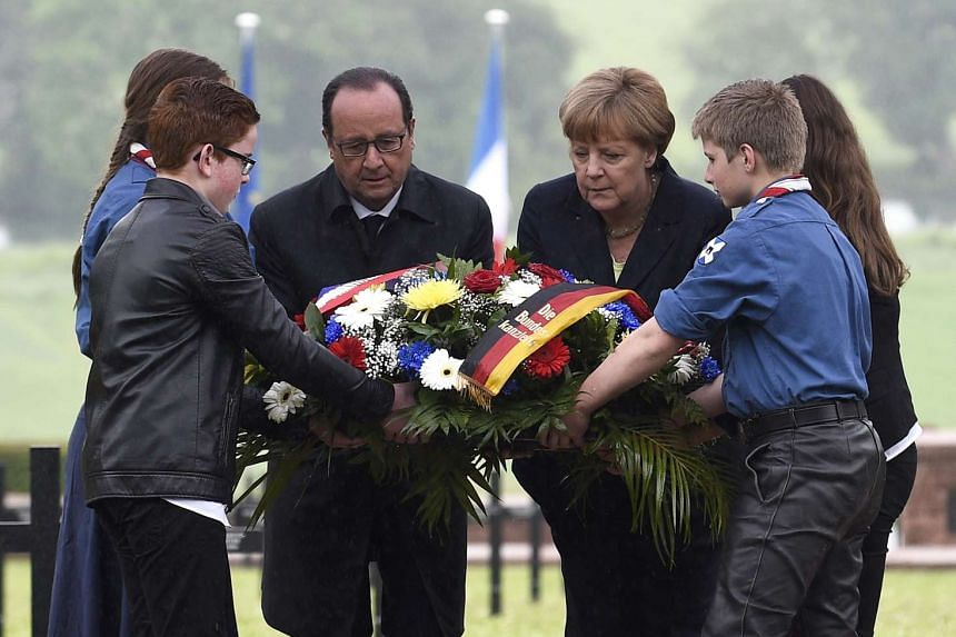French President Francois Hollande (centre left) and German Chancellor Angela Merkel (centre right) lay a wreath at the German military cemetery at Consenvoye, France, on May 29, 2016.