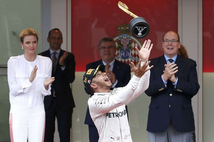 Mercedes F1 driver Lewis Hamilton celebrates after winning next to Prince Albert II of Monaco (right) and Princess Charlene.