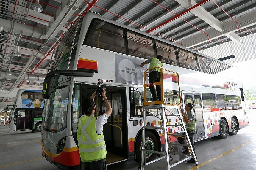 A Tower Transit logo being pasted onto an SMRT bus. The new bus operator is taking over more than 90 buses from SMRT as it launches the first nine of 26 services today. It will take over the remaining 17 services from SBS Transit in two batches next