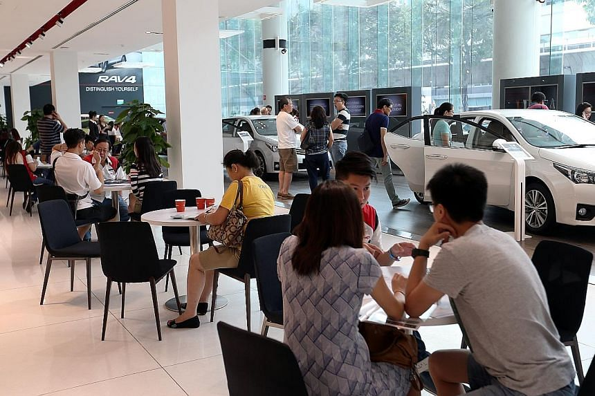 Potential car buyers at the Cycle & Carriage (Mercedes Benz) showroom in Alexandra Road (above) and at Borneo Motors' (Toyota) Leng Kee Showroom (right) yesterday. Both new and used car dealers saw an increase of between 10 and 50 per cent in showroo