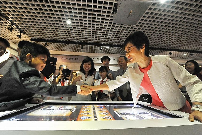 Eight-year-old Trevor Tan shaking hands with Minister for Culture, Community and Youth Grace Fu after she beat him in a multimedia game. Trevor is the great-great-great-grandson of Teo Eng Hock, who was one of the founding members of the Kuomintang.