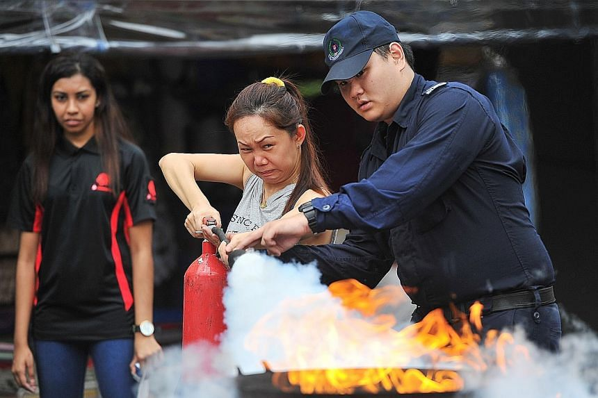 Bank employee Irene Saw, 42, learning how to use a fire extinguisher at the Emergency Preparedness Day held in Chong Pang constituency yesterday. It is the first of six neighbourhoods to pilot the revamped event to help people prepare for possible te
