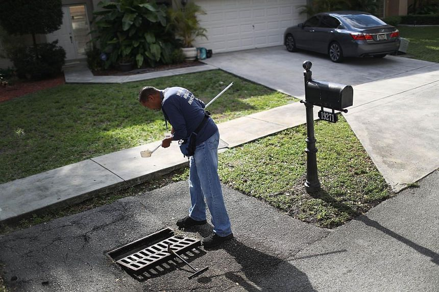 A mosquito control inspector checking for larvae in a drainage ditch in Miami, Florida. There have been 158 reported cases of Zika in the US state. All the patients are believed to have caught the virus while travelling outside the US.