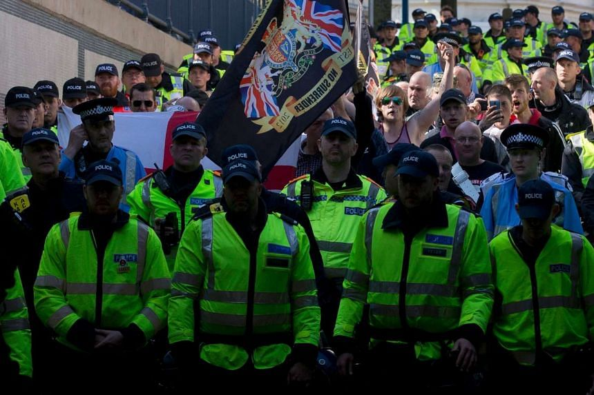 Police personnel escort a demonstration by far-right protesters in the town of Dover in south-east England, on May 28, 2016.