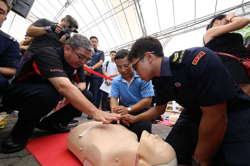 Senior Minister of State Desmond Lee trying out CPR skills at the hands-on training booth on May 29, 2016.