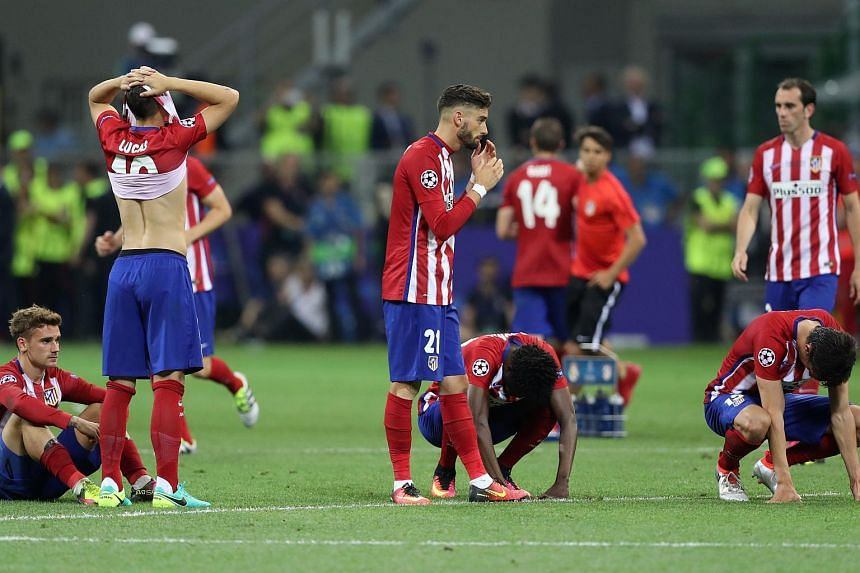 Atletico Madrid players look dejected after the game.