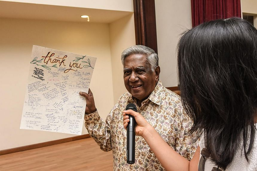 Former President S R Nathan holding up the thank you card that was presented to him after the surprise tribute.