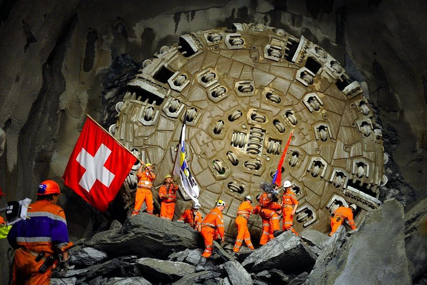 This file photo taken on Oct 15, 2010, shows miners celebrating after a giant drilling machine completed the world's longest tunnel beneath the Swiss Alps.