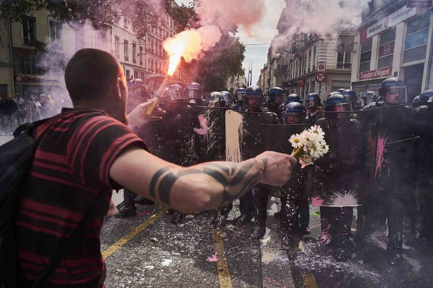 A man holds a bouquet of flowers and a torch as he faces riot police at a demonstration against the government's planned labour reform, on May 26, 2016, in Lyon, France.