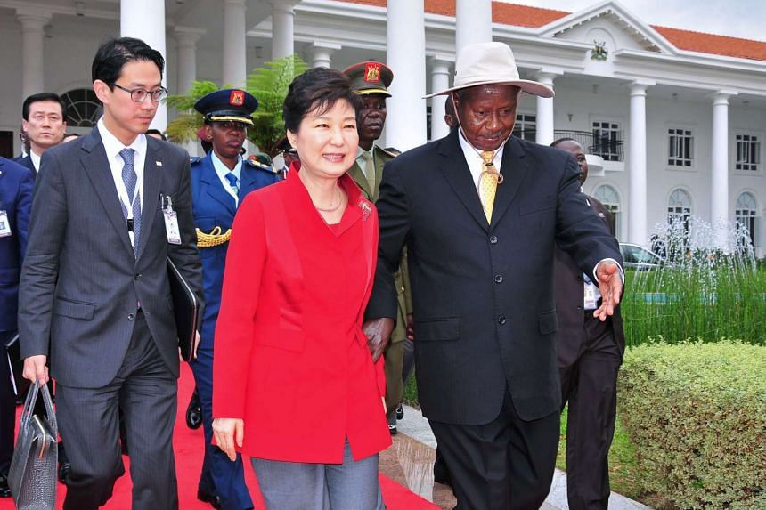 South Korea's President Park Geun Hye (centre) walks with Uganda's President Yoweri Museveni (right) at the State House in Entebbe, on May 29, 2016.