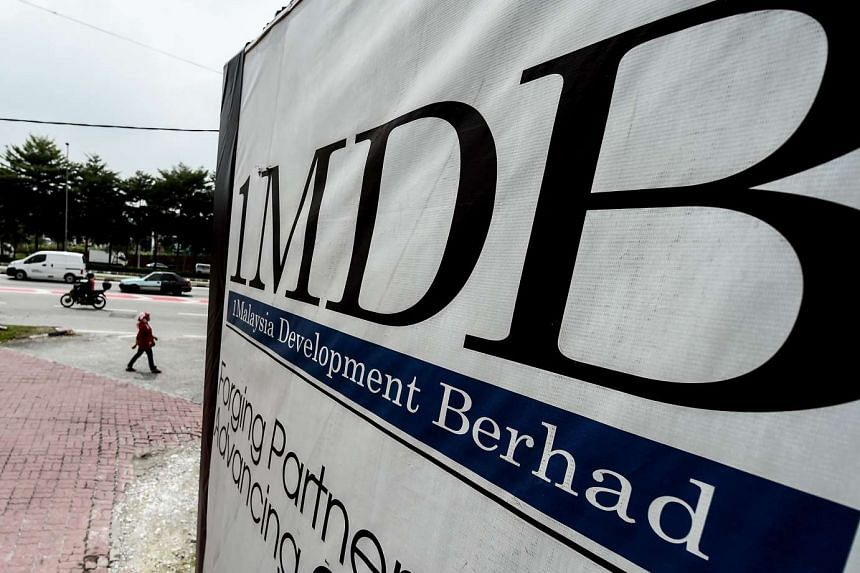 A woman walks past a billboard with the 1 Malaysia Development Berhad (1MDB) logo at the Tun Razak Exchange construction site in Kuala Lumpur, on Sept 22, 2015.