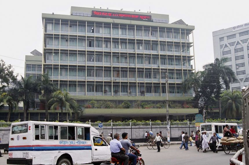 Commuters pass by the front of the Bangladesh central bank building in Dhaka, on March 8, 2016.