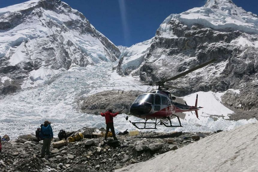 Mountaineers gathering as a helicopter lands at Everest Base Camp, on May 15, 2016.
