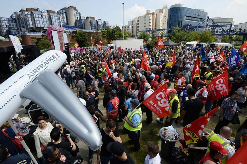 French CGT union's members holding union's flags gather outside the court of Bobigny, France, on May 27, 2016.