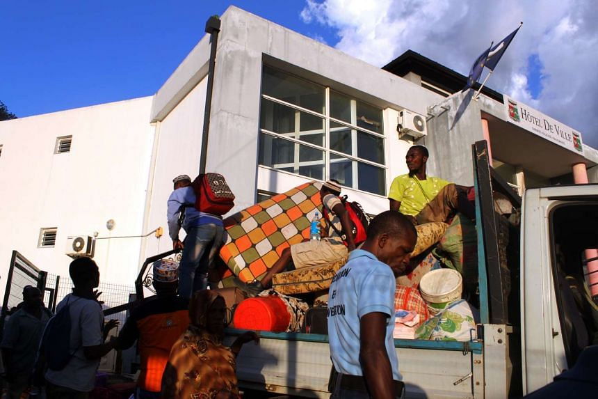 People load their belongings on a pick up on May 29, 2016 in Ouangani, center part of the French overseas region and department Mayotte, to go to the capital, Mamoutzou.